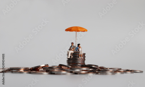 Fotomural  A miniature couple holding a baby sitting with an orange umbrella on a pile of coins
