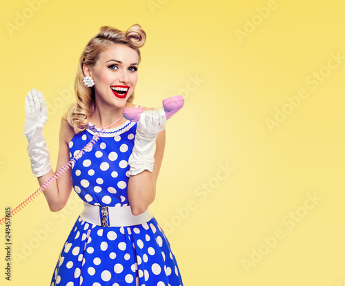 smiling woman with phone, dressed in pin-up style Fototapet