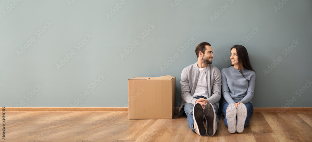Fototapety, obrazy: Young couple sitting on floor near box indoors. Moving into new house