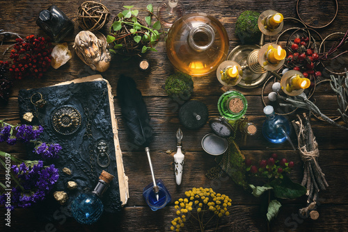 Photo Spell book, magic potions and other various witchcraft accessories on the wizard table background