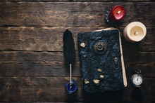 Ancient Magic Book, Pocket Watch And A Black Quill Pen In The Light Of Burning Candle On A Wooden Table Background. Spell Book.