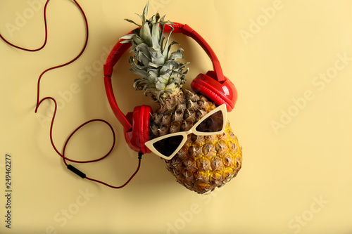 Magasin de musique Funny pineapple with sunglasses and headphones on color background