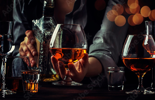 Fotografia The bartender pours the cognac or brandy in big wine glass on the old bar counter