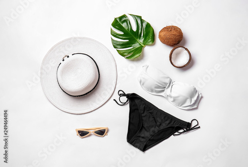 Female swimsuit with accessories, tropical leaf and coconut on white background Canvas Print
