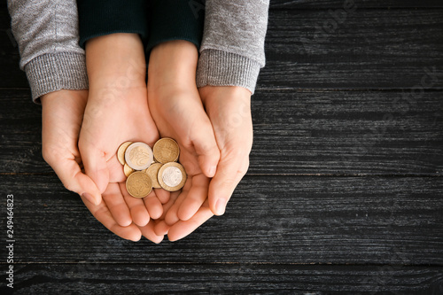 Hands of woman and his son holding coins on wooden table Canvas Print