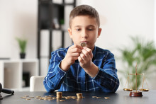 Sad Little Boy With Coins Sitting At Table In Lawyer's Office. Concept Of Child Support