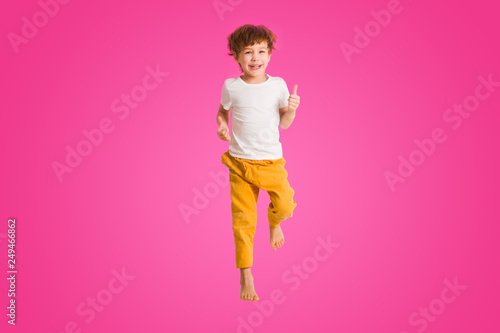 Fotografia Cheerful little boy  jumping on a pink background