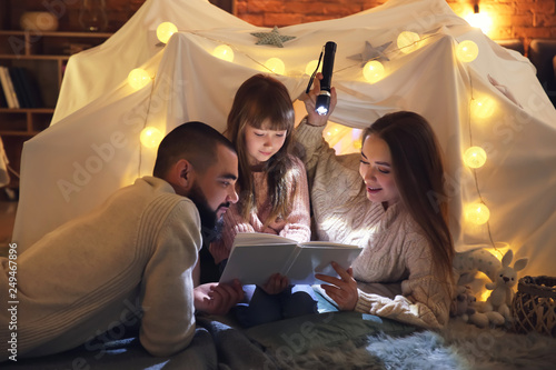 Obraz Happy family reading book at home - fototapety do salonu