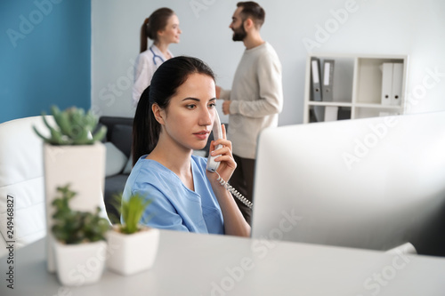 Canvastavla Female receptionist talking by phone in clinic