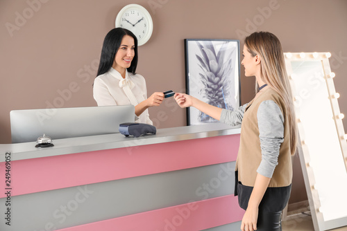 Vászonkép Female receptionist receiving payment for room from client in hotel