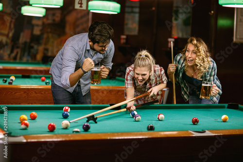 Fototapeta Group of friends playing pool game.