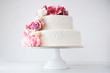 canvas print picture - Two-tiered white wedding cake decorated with pink flowers on a white wooden background.