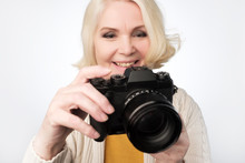 Senior Blonde Woman Taking Photo With Camera
