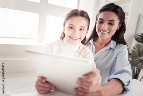 Photographie  Good-looking protecting mother reading junior book to her enthusiastic daughter