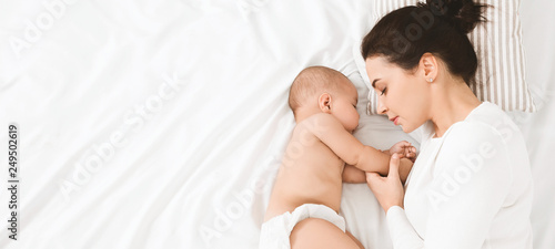 Fototapeta Young mom and her cute baby sleeping in bed obraz