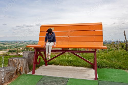 Photo woman sitting on one of the colorful Giant Benches, placed betweenhe vineyards a