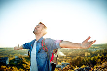 Freedom Concept. Handsome Man Outstretching Arms While Hiking With Backpack
