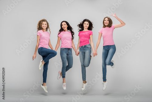Fototapety, obrazy: cheerful girls holding hands and jumping on grey background