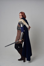 Full Length Portrait Of A  Red Haired Girl Wearing Medieval Warrior Costume And Steel Armour And A Fur Cloak, Standing Pose On Grey Studio Background.