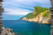 Grotta di Lord Byron with turquoise water and coast with rock cliff through stone wall window, Portovenere town, Ligurian sea, Riviera di Levante, National park Cinque Terre, La Spezia, Liguria, Italy