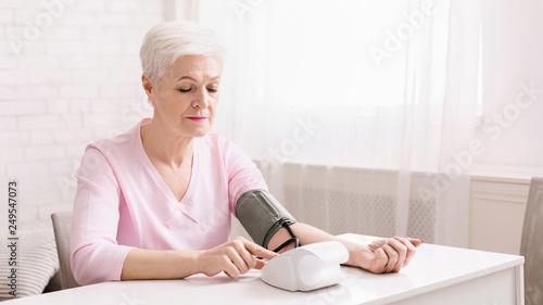 Fotografía  Senior woman measuring her blood pressure at home.
