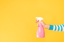 Home Cleaning Chores. Woman Hand Armed With Atomizer. Copy Space On Yellow Background.