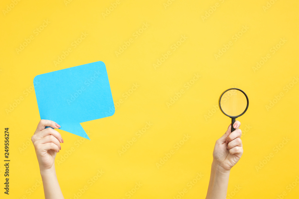 Fototapeta Feedback concept. Assessment survey. Hands holding bubble speech and magnifier. Copy space on yellow background.
