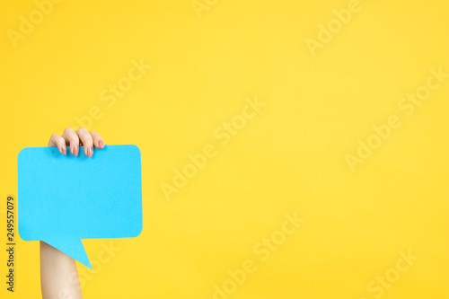 Fototapeta Feedback concept. Hand holding blue speech bubble. Copy space on yellow background. obraz