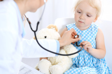Doctor and a little blonde girl. Usual health exam. Medicine and healthcare concept