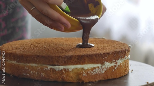 Fotografie, Obraz  Female hand pour the chocolate cream on the cake and begin to spread