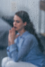 Selective Focus Of Raindrops On Windows With Sad Woman Sitting And Praying On Background