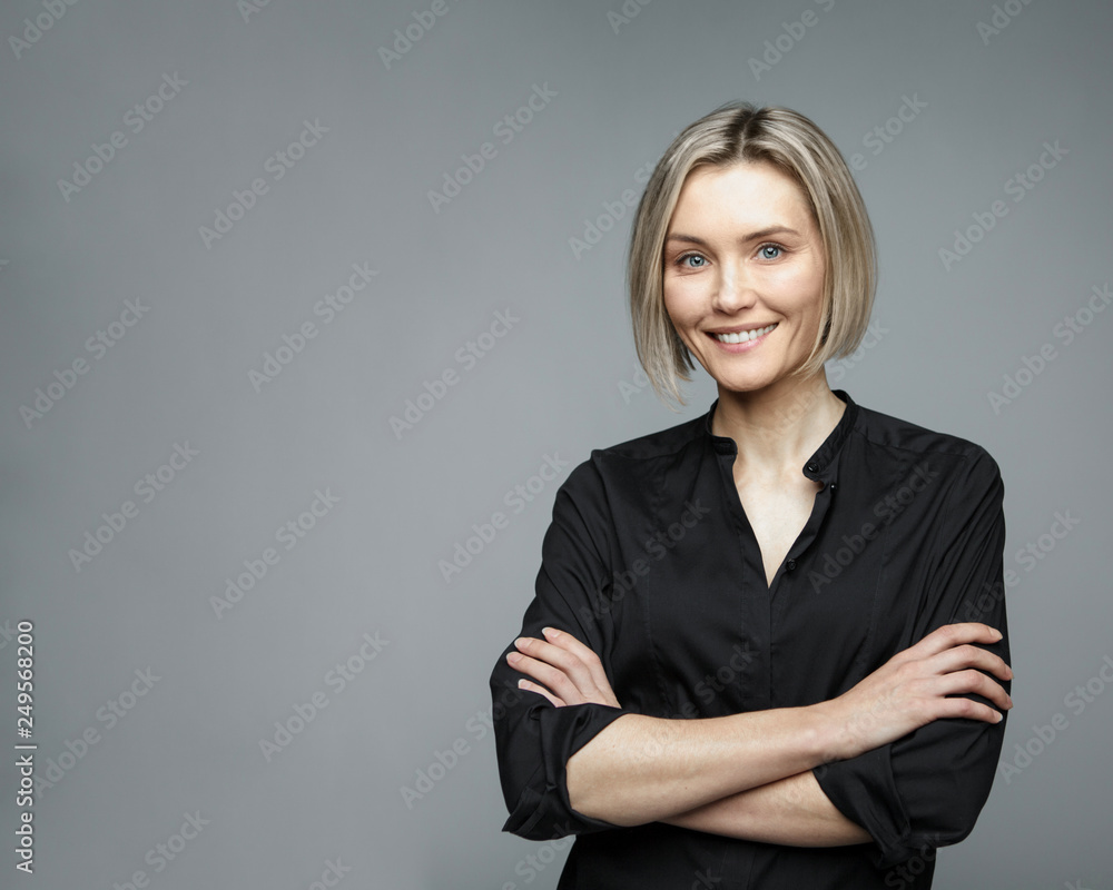 Fototapeta Beautiful middle-aged woman on a gray background in a black blouse smiling.