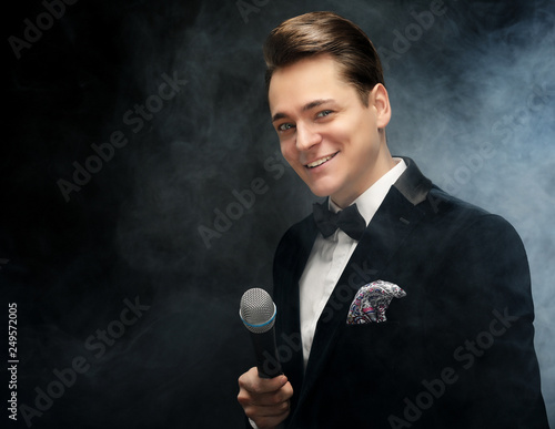 Foto Young handsome man with microphone