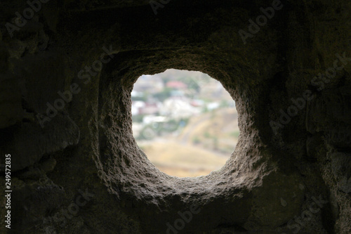 Fotografía  round uneven hole in dark stone wall with white background