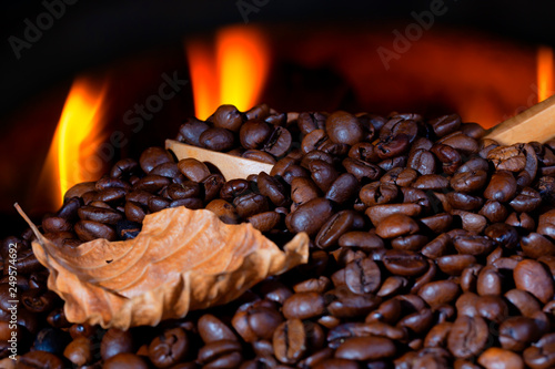 Photo A lot of coffee beans with a wooden spoon and a dry leaf and firelight backgroun