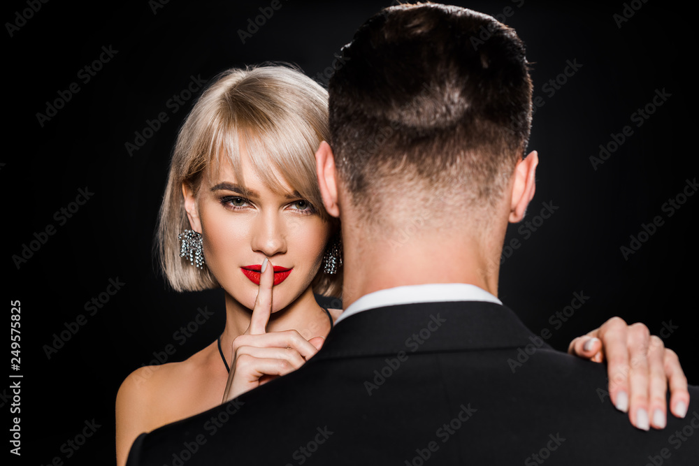 Fototapeta beautiful blonde woman showing silence symbol while standing with boyfriend isolated on black
