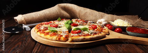 Vegetarian Italian pizza with melted cheese, red tomatoes and green basil on a table decorated by cheese, tomato and cherry tomatoes