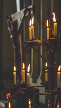 Prayer Candles In Front Of Blurred Jesus On The Cross