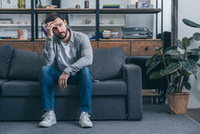 Depressed Man Sitting On Couch, Touching Face And Grieving At Home