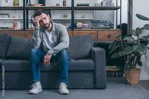 Fotografía  depressed man sitting on couch, touching face and grieving at home