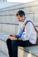 Mature Man Sitting On Steps Using Tablet