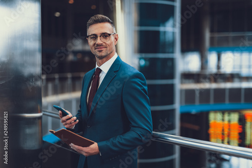 Man with documents and cellular looking at camera and smiling