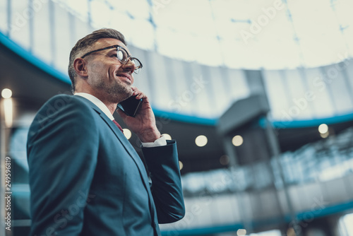 фотографія Man looking aside and speaking on telephone