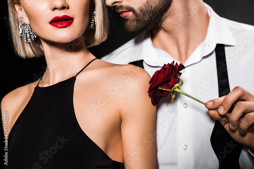 Fotografía  cropped view of man touching womans shoulder with rose flower, isolated on black