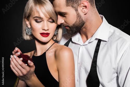 Fototapeta handsome man hugging girlfriend with rose flower, isolated on black obraz