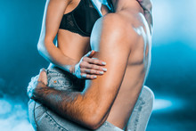 Cropped View Of Man Hugging Sensual Girl On Blue Smoky Background