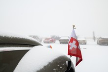 Snow Covered Old Classic Car With Swiss Flag