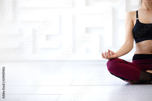 Woman sitting of meditation in the lotus position close-up.