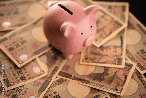 Photo 豚の貯金箱とお金のイメージ
