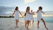 Young Caucasian parents and daughters walking on a beach at sunrise